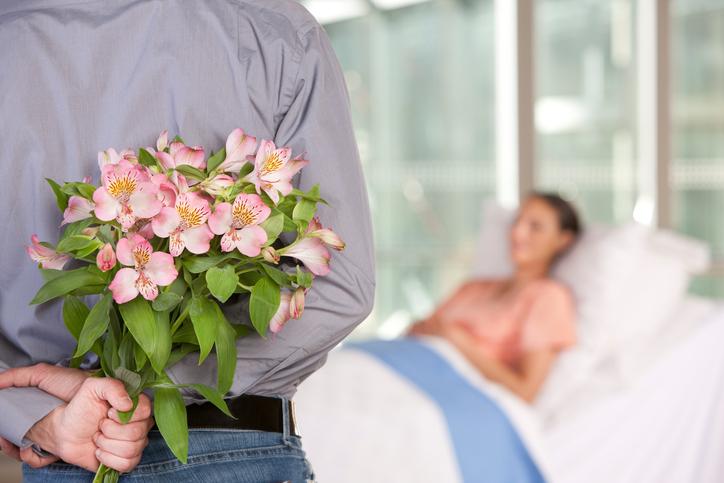 Foto: Mann bringt Blumen zu seiner Frau ins Krankenhaus